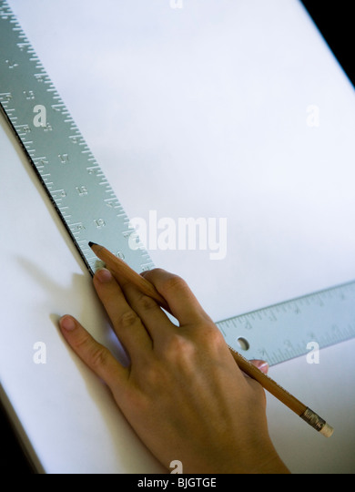 hand using a square on a drafting table - Stock Image
