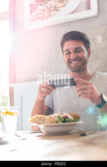 Smiling man photographing lunch at cafe table - Stock Image