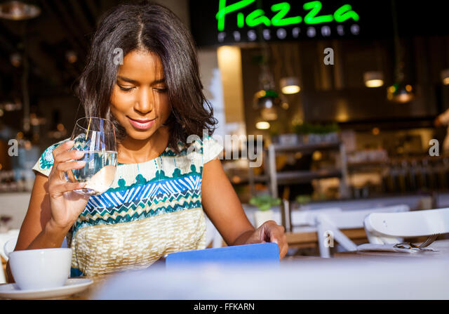 Mixed race woman sits in cafe using computer - Stock Image