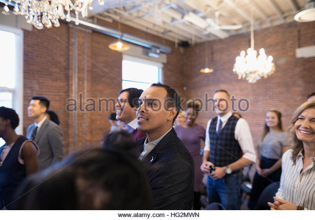 Smiling businessman listening in conference audience - Stock Image