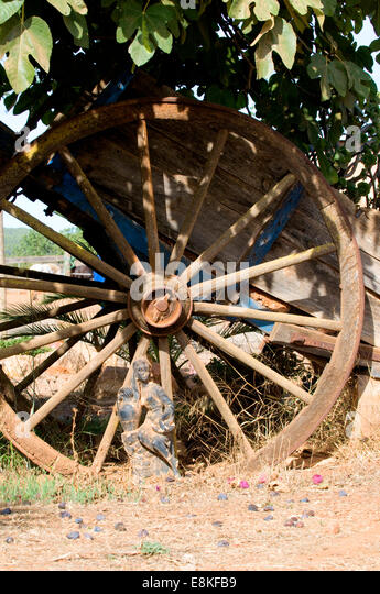 Sun drenched rustic agricultural cart's wheel standing under Mediterranean Fig tree with small figurine placed - Stock-Bilder