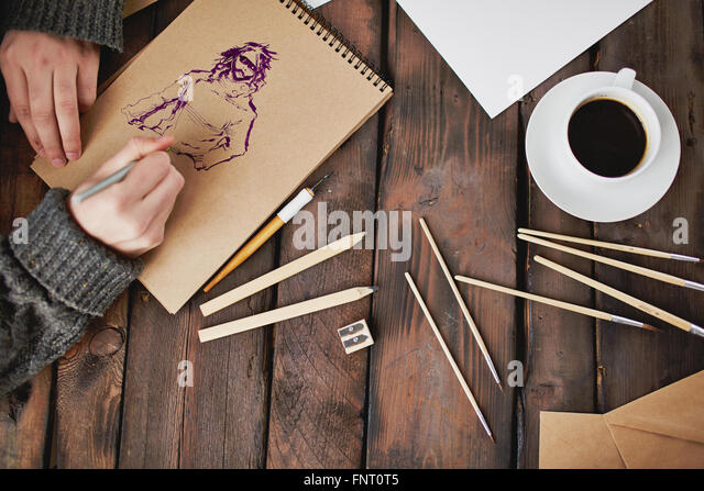 Close-up of man painting a picture at his workplace - Stock Image