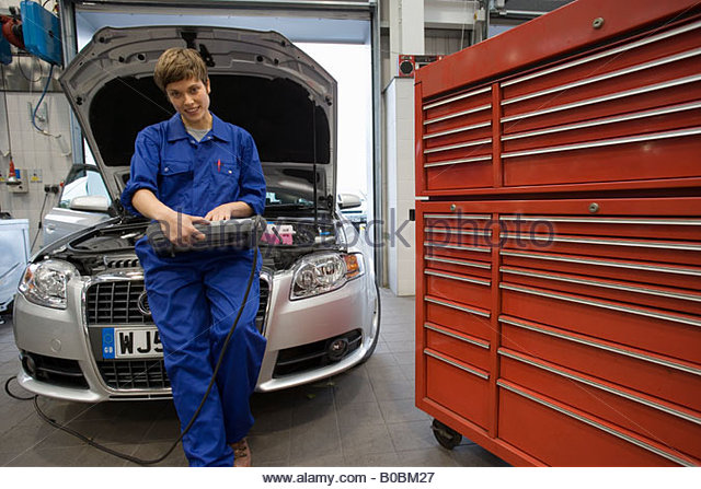 Female mechanic with diagnostic computer by open bonnet of car - Stock Image