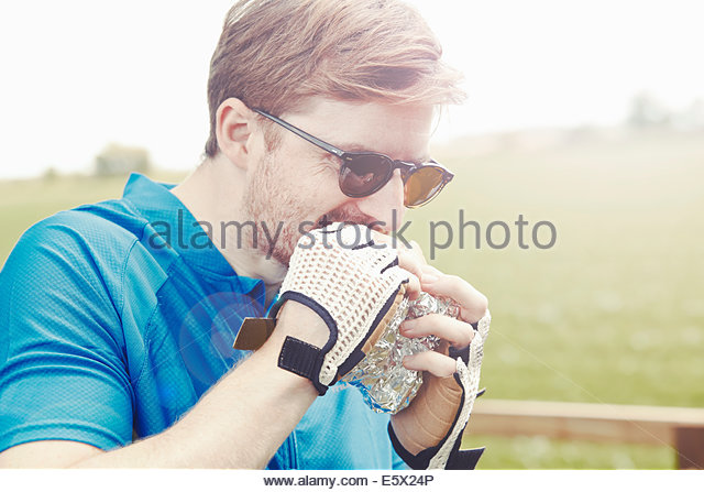 Cyclist eating sandwich with gloved hands - Stock Image
