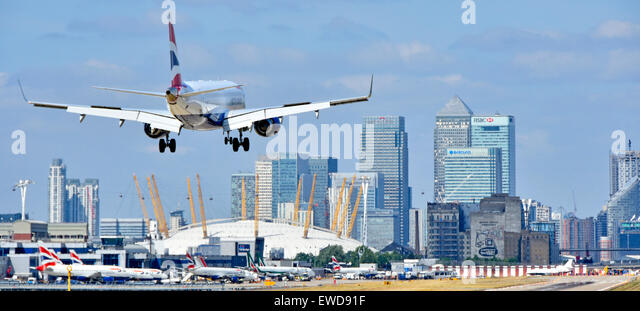 British Airways flight landing at London City Airport Newham with O2 arena & Canary Wharf skyline Tower Hamlets - Stock Image