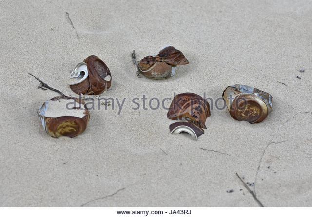 Corroded cans in the sand - Stock Image