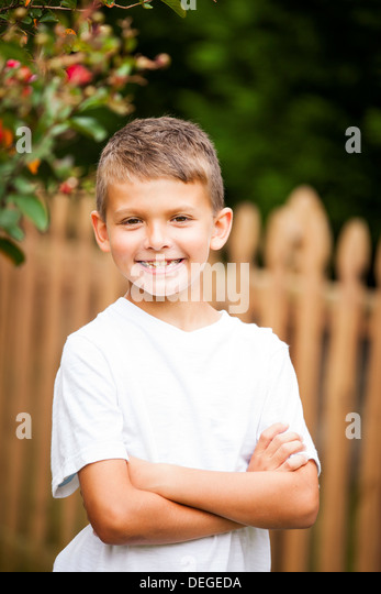 boy crossing arms and smiling - Stock Image