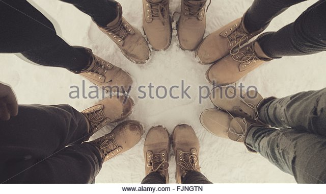 Low Section Of Friends Standing On Snow Covered Field - Stock Image