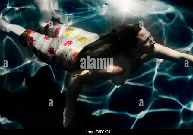 Woman swimming in sarong - Stock Image