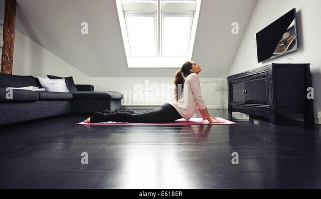 Young brunette woman working out stretching exercise on floor. Fitness female model exercising on mat at home. - Stock-Bilder
