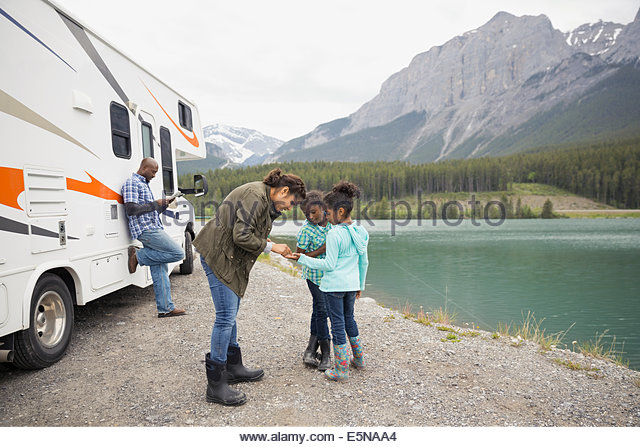Family standing at lakeside near RV - Stock Image