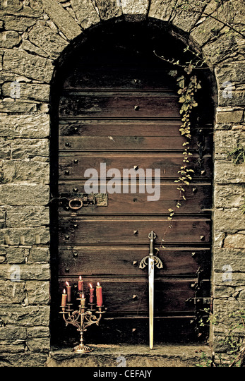 a candleholder and a sword in front of an old wooden door - Stock Image