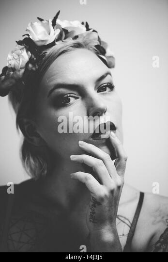 Young tattooed woman wearing a flower crown - Stock Image