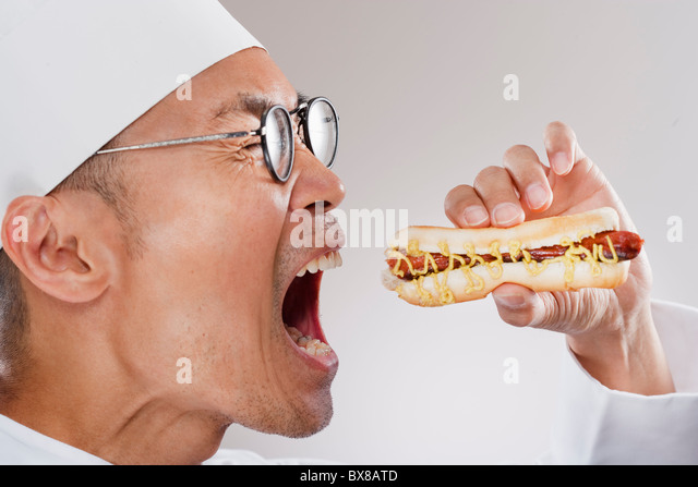 Chef about to eat a hotdog - Stock-Bilder