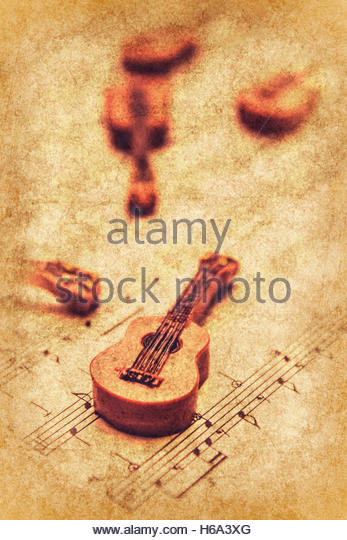Vintage musical concept on old textured guitars laying on sheet music. Art of classical rock - Stock Image