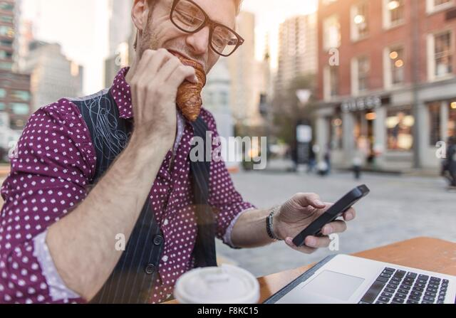 Stressed young businessman reading smartphone whilst eating at sidewalk cafe, New York, USA - Stock-Bilder