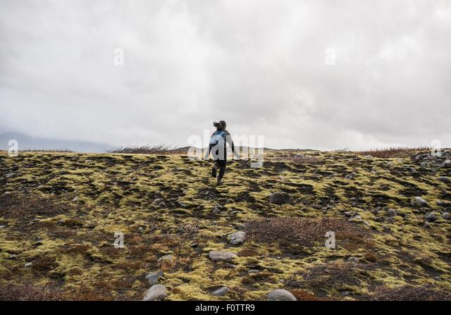 Rear view of female tourist running across moorland,  Skaftafell, Iceland - Stock Image