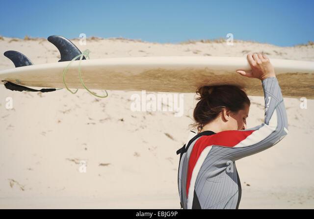 Surfer carrying surfboard on head at beach, Lacanau, France - Stock-Bilder