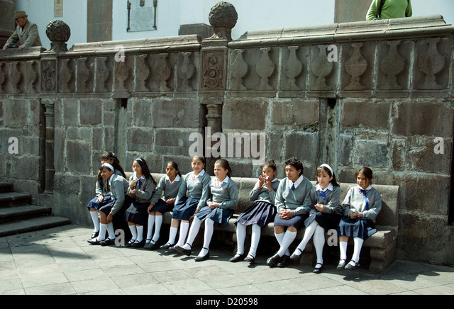 Smartly uniformed schoolgirls sitting on a bencn in the Plaza de la Independencia Quito - Stock Image