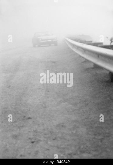 Car on street in fog - Stock Image