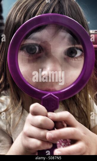 Toddler girl looking through magnifying glass - Stock Image