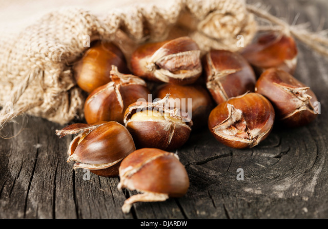 Roasted chestnuts in burlap bag on wooden background - Stock Image
