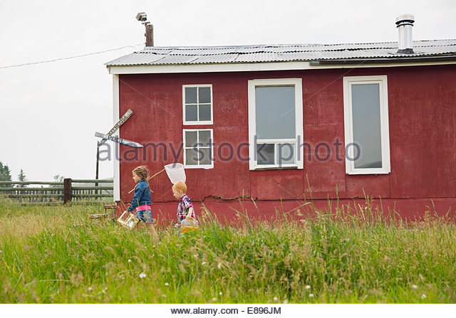 Brother and sister with butterfly net outside house - Stock Image