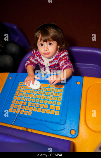Little girl playing with a children computer - Stock Image