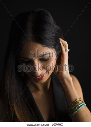 Smiling Indian woman with bindi looking down against black background - Stock Image
