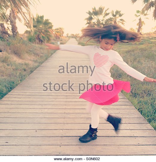 Girl turning at sunset surrounded by palm trees - Stock-Bilder