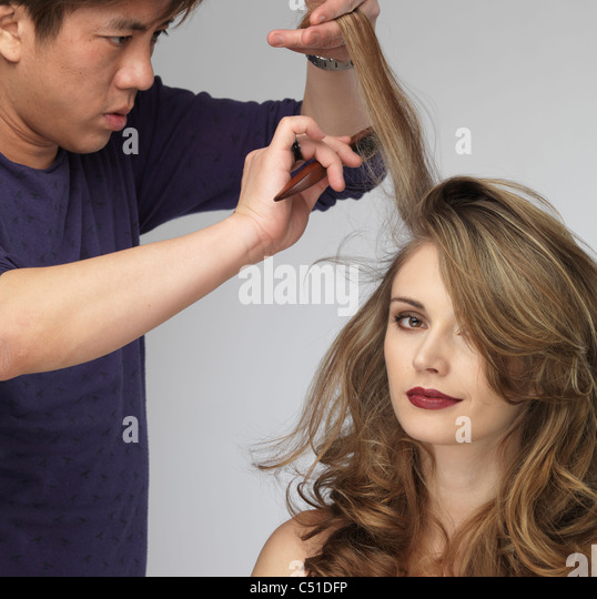 Hairstylist teasing young beautiful woman's hair - Stock Image