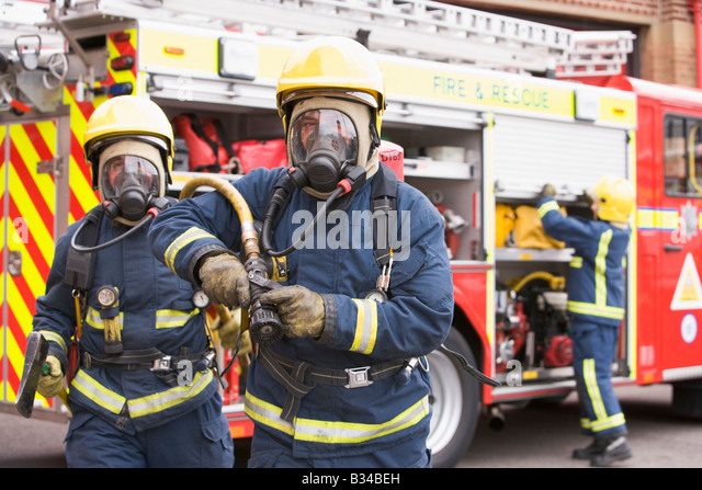 Two firefighters with hose and axe walking away from fire engine and another firefighter in background (selective - Stock Image