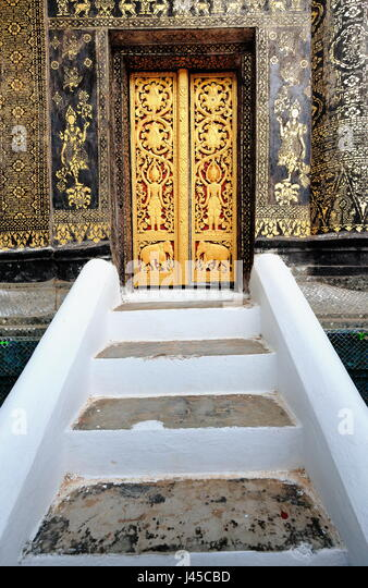 Gilded carved teakwood door closed-white stairway-rear facade of the sim-viharn-assembly-congregation hall in the - Stock-Bilder