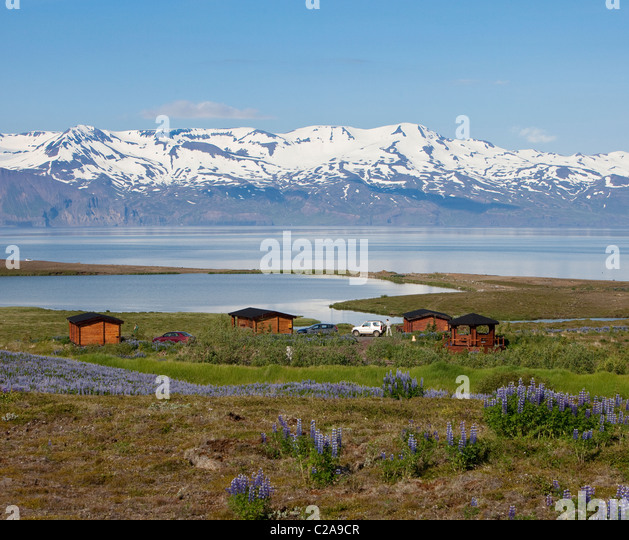 Summer house overlooking water and mountains, Skjalfandi bay, Tjornes Peninsula, Iceland - Stock Image