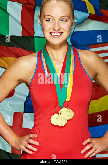 Young woman in front international flags wearing medals - Stock-Bilder