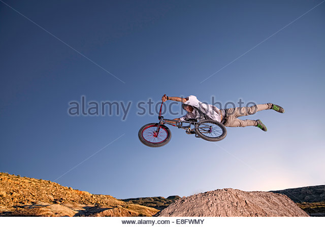 Low angle view of young man on BMX bike jumping mid air - Stock Image