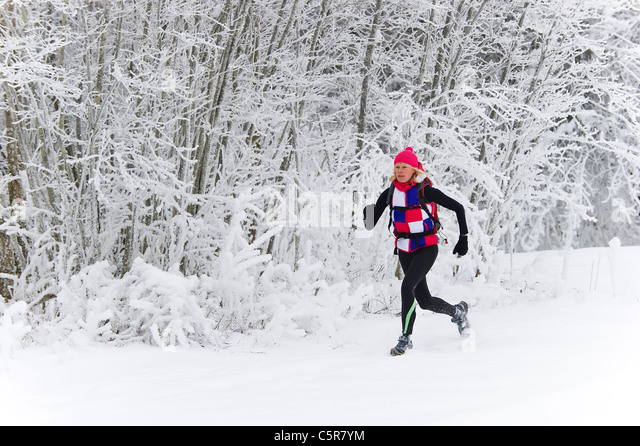 Jogging through a snow covered forest. - Stock-Bilder