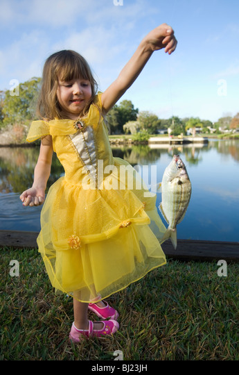 A girl holding a fish - Stock Image