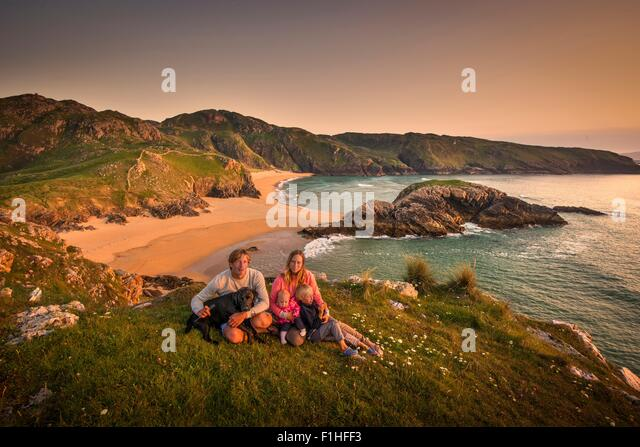 Portrait of family sitting on hillside, Murder hole beach, Melmor Head, Ireland - Stock-Bilder