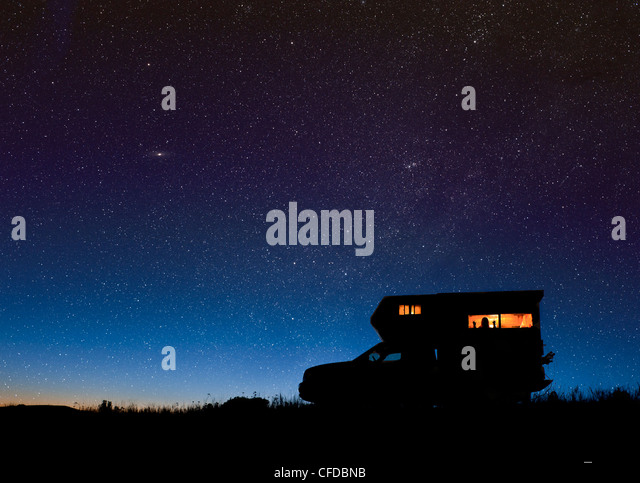 Camper under starry sky near Merritt, British Columbia, Canada. Cassiopea and the Andromeda galaxy are visible. - Stock Image