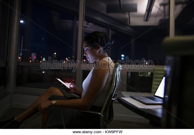 Focused,dedicated businesswoman texting with smart phone in dark conference room - Stock Image