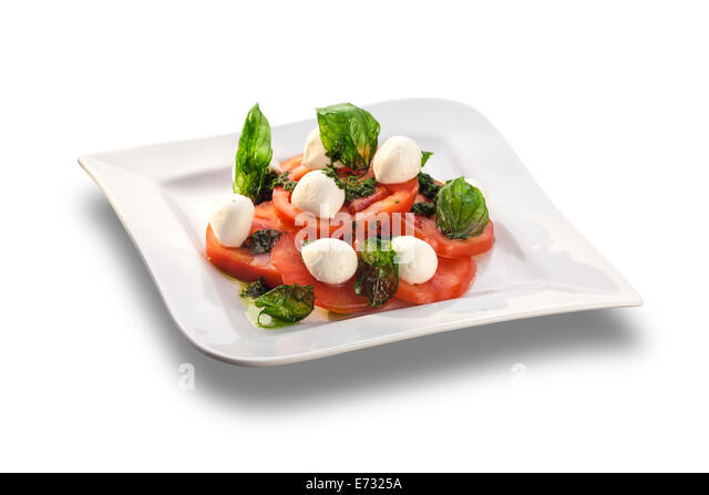 Artistically arranged tomato salad with mozzarella garnished with basil isolated on white plate - Stock-Bilder