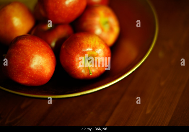 Bowl of apples on table - Stock Image