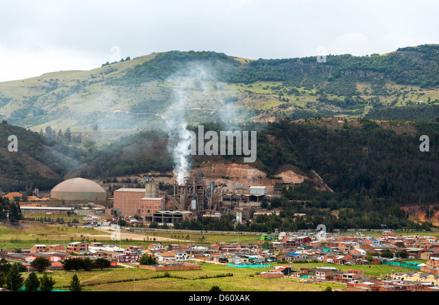 A factory producing pollution near a small town - Stock Image
