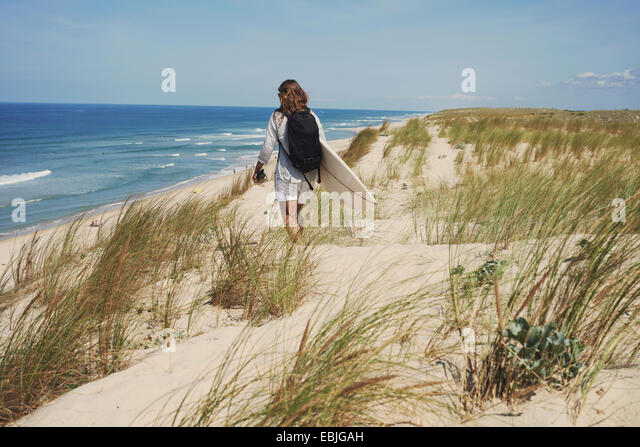 Woman with surfboard on beach, Lacanau, France - Stock-Bilder