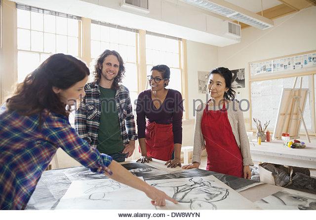 Students analyzing charcoal drawings in art studio - Stock-Bilder