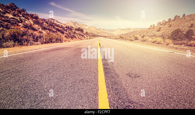 Retro vintage old film style endless country road, travel adventure concept, space for text, USA. - Stock-Bilder