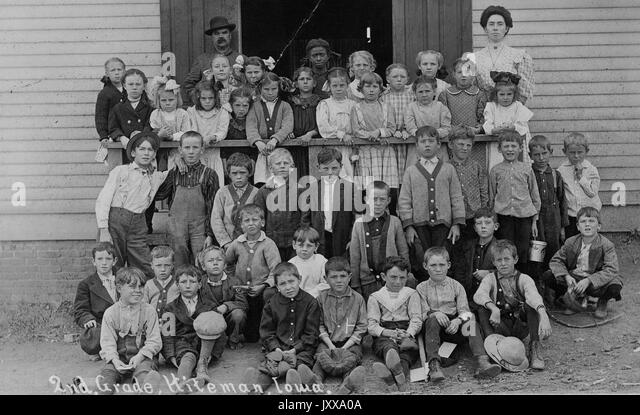 Full length landscape shot of schoolchildren seated and standing outdoors, African American students 'in last - Stock Image