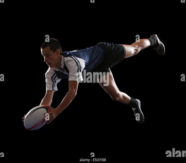 Studio portrait of teenage boy (14-15) with rugby ball - Stock Image