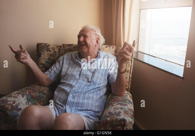 Indoor shot of happy old man sitting on a arm chair and  smiling. Senior man relaxing at old age home. - Stock Image